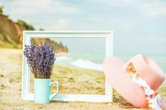 淡紫色花、木制框架和桃红色海滩帽子在沙子 免版税库存图片