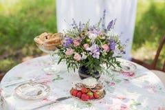 淡紫色花在餐桌上的户外 免版税库存图片