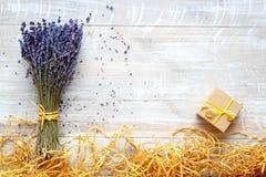 淡紫色花束与礼物盒的在木桌上 免版税库存图片