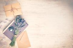 淡紫色花束放置了在一本旧书、一个被包裹的礼物盒、牛皮纸信封和银色心脏在一白色木backgroun 免版税库存图片