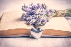 淡紫色花束放置了在一本旧书和银色心脏在白色木背景 例证百合红色样式葡萄酒 免版税库存照片