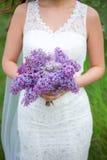 淡紫色花花束在新娘的手上 免版税库存照片