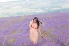 淡紫色领域和一名愉快的孕妇 库存照片
