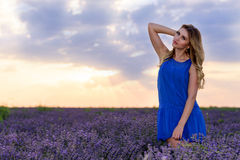 淡紫色领域的女孩在日落 免版税库存图片
