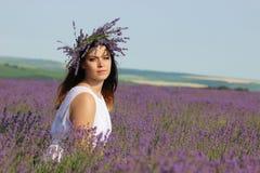 淡紫色领域的少妇 免版税库存照片