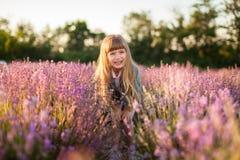 淡紫色领域的微笑的女孩 免版税库存照片