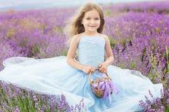 淡紫色领域的愉快的小女孩与篮子 图库摄影