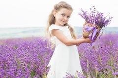 淡紫色领域的愉快的小女孩与篮子  免版税库存照片