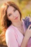 淡紫色领域的美丽的女孩 库存图片