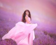 淡紫色领域的美丽的少妇 桃红色裙子,一种好心情 库存照片