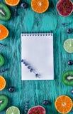 淡紫色,笔记本,猕猴桃,柑橘,在蓝色背景顶视图嘲笑的无花果 免版税库存图片