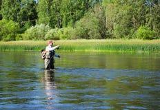 淡水鳔形鱼用假蝇钓鱼渔夫抓住在Chusovaya河 免版税库存图片