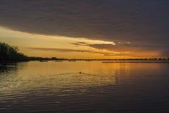 深刻的橙色日出在风雨如磐的多云天空下,反映在安静 免版税库存图片