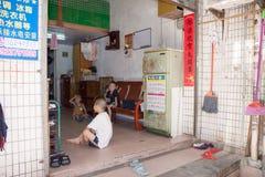 深圳,中国, 2011-07-24 :中国孩子在他们的房子大厅里在城市的恶劣的区 库存图片