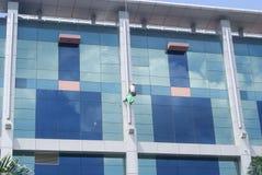 深圳,中国:工作者清洗在高层建筑物的玻璃悬墙 图库摄影