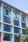 深圳,中国:工作者清洗在高层建筑物的玻璃悬墙 免版税库存图片