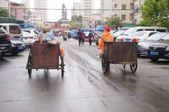 深圳,中国:拖拉垃圾车的卫生工作者 免版税图库摄影