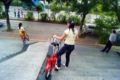 深圳,瓷:运载自行车的两个女孩去下坡 库存照片