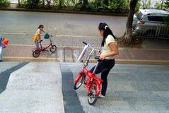 深圳,瓷:运载自行车的两个女孩去下坡 库存图片