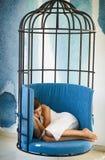 深度域浅休眠的妇女 在铁栅栏的妇女睡眠 甜点和舒适梦想,早晨 现代家具设计和家庭舒适 库存图片