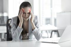 深度服务台领域重点玻璃头疼办公室专业浅开会重点强调疲乏的妇女工作年轻人 年轻女商人画象在 免版税库存图片