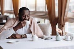 深情的非裔美国人的在咖啡馆的人饮用的茶 免版税库存图片