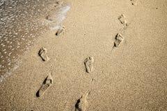 深深脚印在沙子,错觉 免版税库存图片