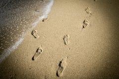 深深脚印在沙子,错觉 库存照片