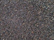 深灰沙子表面,湿海滩有火山的沙子背景 免版税图库摄影