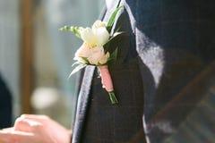 深灰衣服的新郎与一朵白色玫瑰钮扣眼上插的花 关闭在太阳射线的射击 库存图片