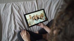 深色头发的女孩与朋友谈话网上使用看显示,打手势和摇手的片剂 现代 股票录像