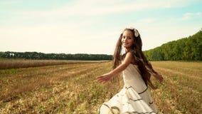 深色头发的女孩在一件长的礼服被转动 慢的行动 白色礼服跳舞的女孩在领域 快乐的子项 股票视频