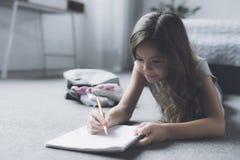 深色头发的女孩在地板上说谎在床旁边并且画某事与在她的白色图画书的一支铅笔 免版税库存图片