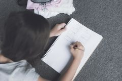 深色头发的女孩在地板上说谎并且画在白色笔记本的一支铅笔有铅笔计划的 库存图片