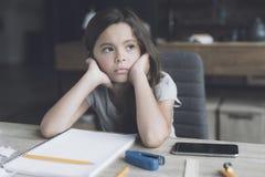 深色头发的女孩坐在她的有一个乏味表示的书桌 在它旁边是一个白色笔记本和她的智能手机 免版税库存图片