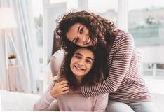 深色头发的女孩感觉爱,当拥抱她有同情心的姐妹时 免版税库存图片