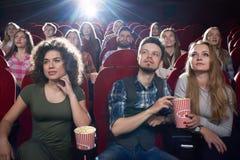 深色女孩和夫妇享用电影有意思 免版税图库摄影