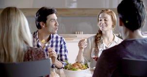 深色男人和红头发人妇女谈话 四个愉快的真正的坦率的朋友一起喜欢吃午餐或晚餐在家或 股票录像