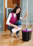 深色的与洗涤剂的女孩洗涤的地板 免版税库存图片