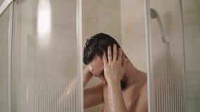 深色的人在家,特写镜头洗涤在一场阵雨的头 股票录像
