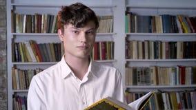 深色的人是阅读书,观看在照相机,背景的图书馆 影视素材