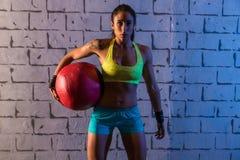 深色的健身房女孩藏品被衡量的球 免版税库存图片