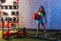 深色的健身房女孩藏品被衡量的球 图库摄影
