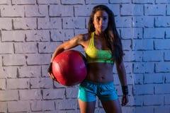 深色的健身房女孩藏品被衡量的球 库存图片