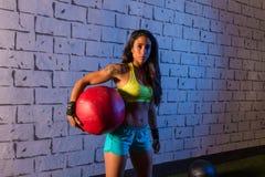 深色的健身房女孩藏品被衡量的球 库存照片