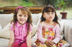 深色的儿童姐妹愉快地坐白色 图库摄影