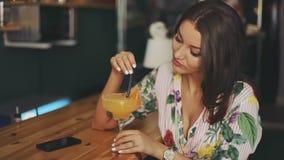 深色的可爱的妇女坐的酒吧夜总会饮用的酒精橙色鸡尾酒淡黄色礼服休闲放松 影视素材