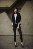 年轻深色的在黑夹克,佩带小山的牛仔裤的妇女常设外部 水平 免版税库存图片