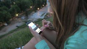 深色的女孩使用一个智能手机,移动并且调整照片 股票视频