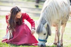 深色的女孩和马 免版税库存图片
